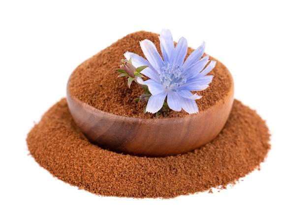 Poudre de chicorée et fleur dans un bol en bois, isolé sur fond blanc. cichorium intybus.