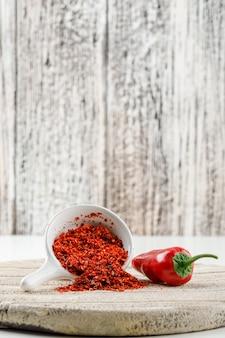 Poudre de chili au poivron rouge et pièce en bois dans une cuillère blanche sur mur grunge blanc et bois, vue latérale.