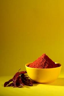 Poudre de chili dans un bol jaune. poivron rouge frais