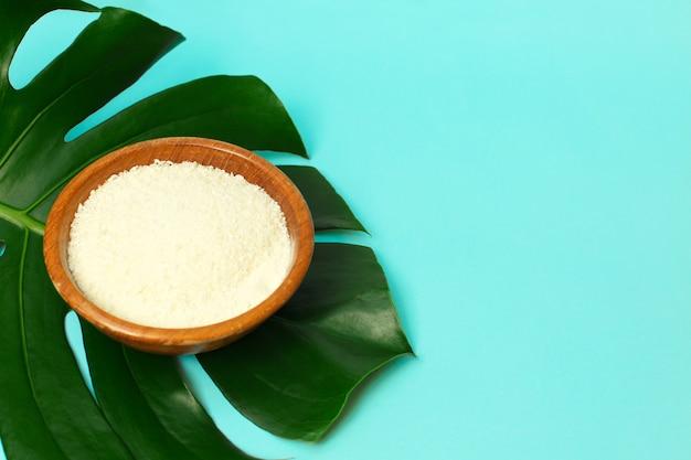 Poudre de collagène dans un bol sur fond de feuille de palmier.