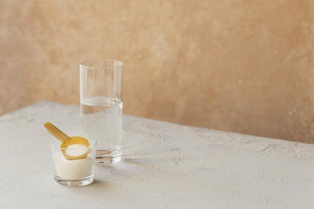 Poudre de collagène dans un bol, verre d'eau et cuillère mesure sur un fond en bois blanc. apport supplémentaire de protéines. concept de supplément de beauté et de santé naturelle.