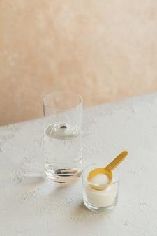Poudre de collagène dans un bol, verre d'eau et mesure cuillère sur blanc