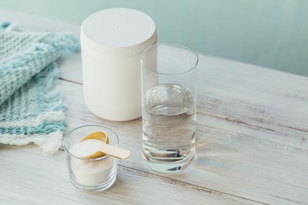 Poudre de collagène dans un bol, verre d'eau et mesure cuillère sur un fond bleu clair. apport supplémentaire de protéines. concept de supplément de beauté et de santé naturelle.