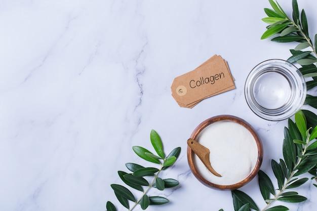 Poudre de collagène sur un fond de marbre tendance avec des feuilles d'olivier vertes. complément naturel de beauté et de santé, concept anti-âge de soins de la peau bien-être. vue de dessus, mise à plat, espace de copie