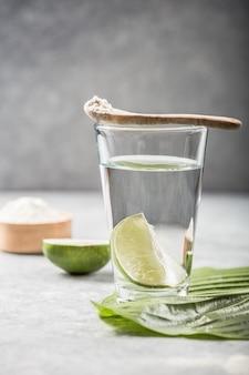 Poudre de collagène et verre d'eau avec tranche de citron vert