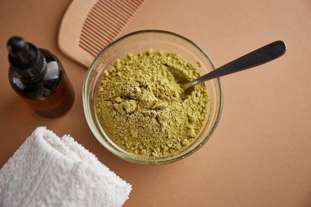 Poudre de colorant henné mehndi dans un bol en verre et un peigne en bois, vue du dessus. produits de soins capillaires ayurvédiques. soin naturel et coloration des cheveux.