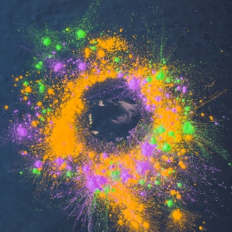 Poudre colorée dispersée sur une table sombre