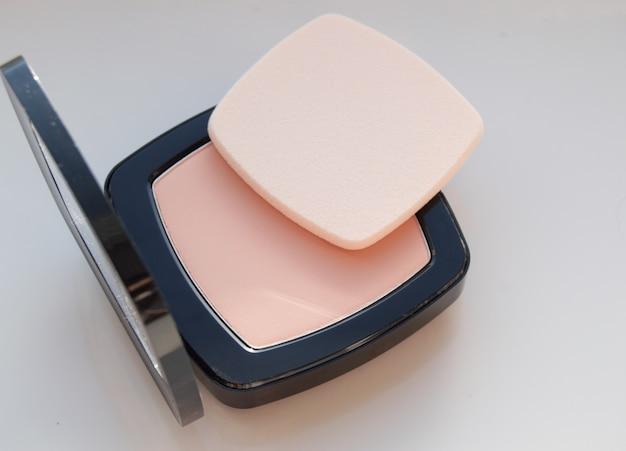 Poudre compacte avec bouffée pour le maquillage, sur fond blanc, vue de dessus