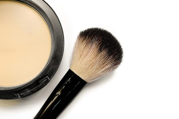 Poudre compacte minérale avec un pinceau pour l'application, isolée sur fond blanc.