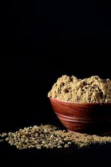 Poudre de coriandre dans un bol en bois avec des graines