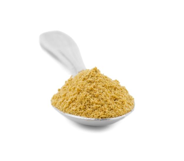 Poudre de coriandre ou poudre de dhaniya en cuillère sur fond blanc