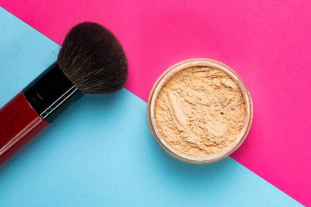 Poudre cosmétique légère pour femmes avec un pinceau sur une double surface de papier rose et bleu