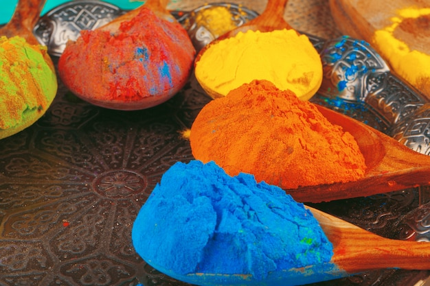 Poudre de couleurs holi indiennes traditionnelles, épices sur un mur rustique foncé