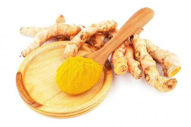 Poudre de curcuma et curcuma frais dans une cuillère en bois sur fond blanc.