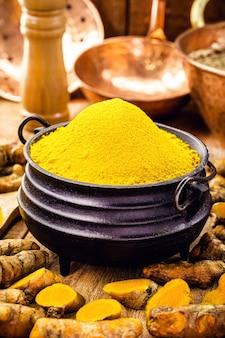 Poudre de curcuma dans des bols en métal fondu sur table en bois. ingrédient culinaire