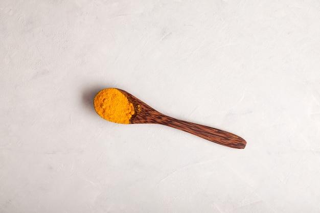 Poudre de curcuma jaune dans une cuillère en bois sur fond clair espace copie vue de dessus