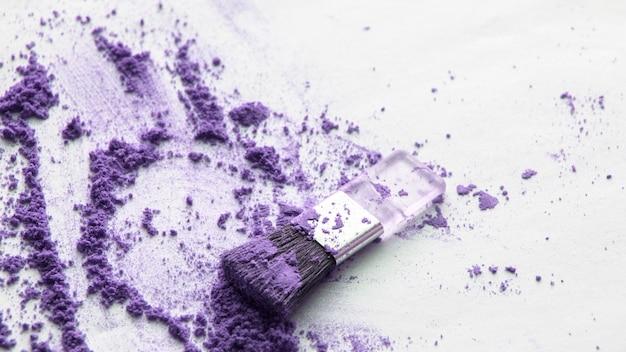 Poudre éparse violet avec un pinceau pour appliquer le maquillage sur un fond blanc isolé, maquillage de beauté supérieure