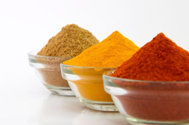 Poudre d'épices: chili, curcuma et coriandre dans un bol isolé.