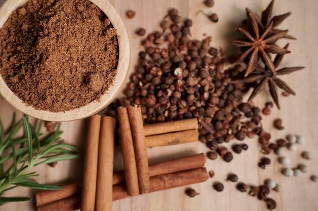 Poudre et épices de ragoût dans une tasse en bois avec le fond noir, concept d'industrie