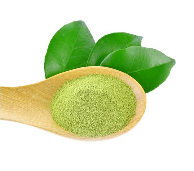 Poudre ou feuille de thé vert sur le fond blanc
