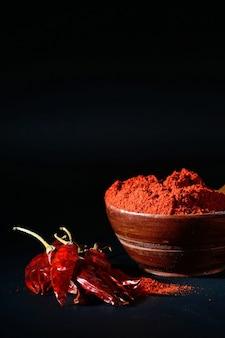 Poudre fraîche dans un bol en bois avec des piments rouges séchés et frais