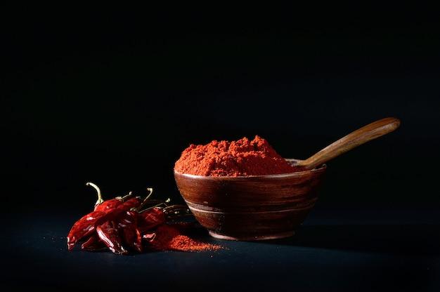 Poudre fraîche dans un bol en bois avec des piments séchés et chilly rouge sur fond noir