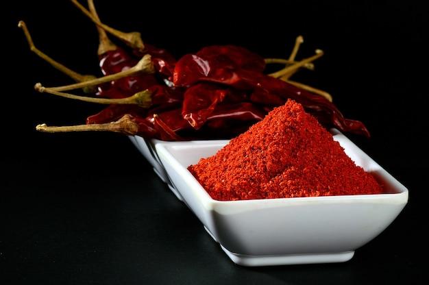 Poudre froide avec du frisson rouge en plaque blanche, piments séchés sur fond noir