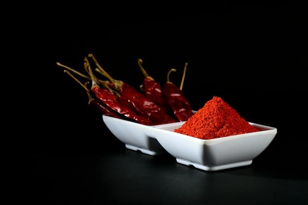 Poudre froide avec frisquet rouge en plaque blanche, piments séchés sur fond noir