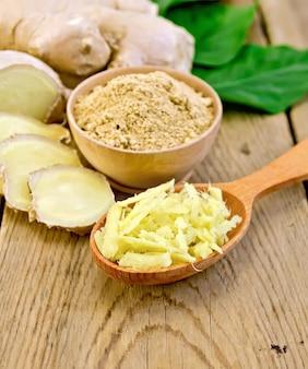 Poudre de gingembre dans un bol, cuillère en bois avec gingembre râpé, racine de gingembre, feuilles vertes sur fond de planches de bois