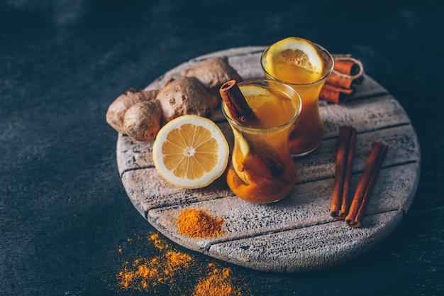 Poudre de gingembre dans des tasses à thé avec citron, gingembre et cannelle sèche high angle view on wood sur un fond texturé sombre