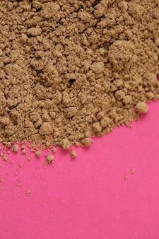 Poudre de guarana sur fond rose. super nourriture. naturel énergétique.