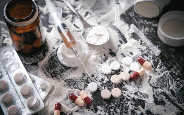Poudre d'héroïne, pilules et seringue sur fond sombre.