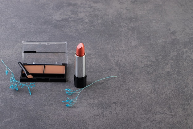 Poudre de maquillage dans un boîtier en plastique rond noir avec rouge à lèvres et pinceaux.