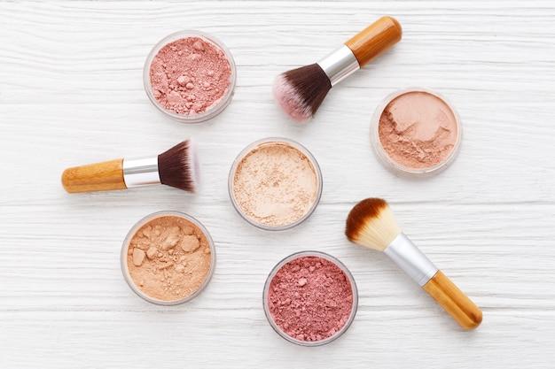 Poudre de maquillage avec des pinceaux sur une table en bois blanche