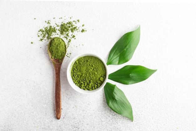 Poudre de matcha de thé vert sur tableau blanc
