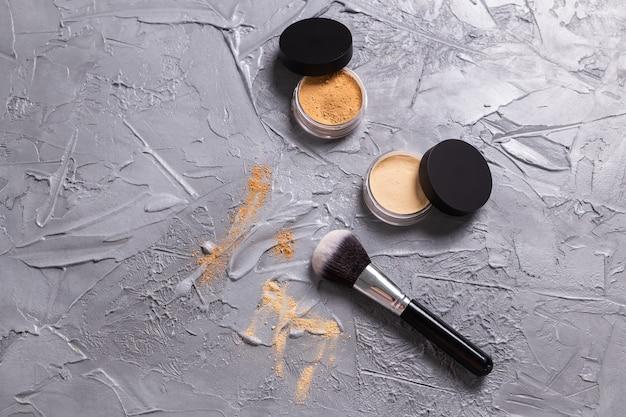 Poudre minérale de différentes couleurs avec un pinceau pour le maquillage sur fond de bois