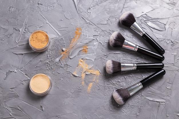 Poudre minérale de différentes couleurs avec un pinceau pour le maquillage sur la vue de dessus de fond en bois