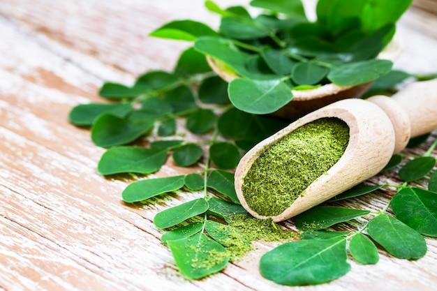 Poudre de moringa dans une cuillère en bois avec des feuilles de moringa fraîches originales