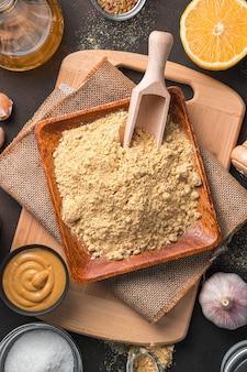 Poudre de moutarde dans une assiette en bois sur une planche à découper sur un fond marron. vue de dessus.