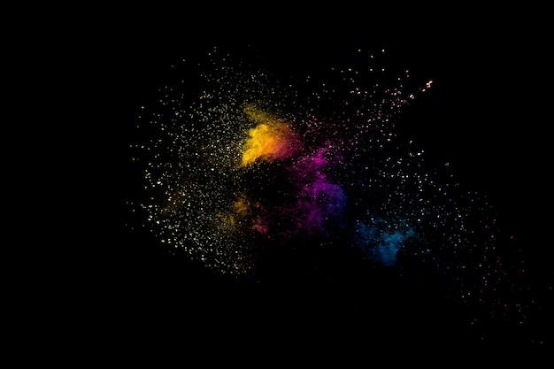 Poudre multicolore lancée sur fond noir. explosion de poudre de couleur. éclaboussures de poussière colorées.