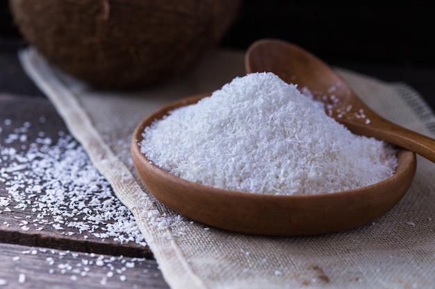 Poudre de noix de coco d'une noix de coco dans le panier sur la table à l'intérieur de la cuisine pour faire du lait de coco