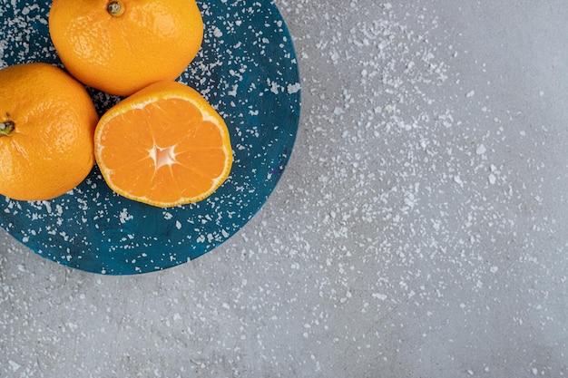 Poudre de noix de coco saupoudrée et un plateau d'oranges sur table en marbre.