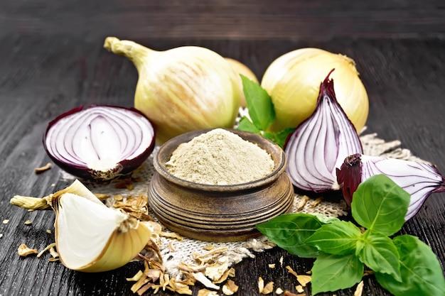 Poudre d'oignon dans un bol sur une serviette en toile de jute, oignons violets et jaunes, flocons d'oignons séchés et basilic frais sur fond de planche de bois