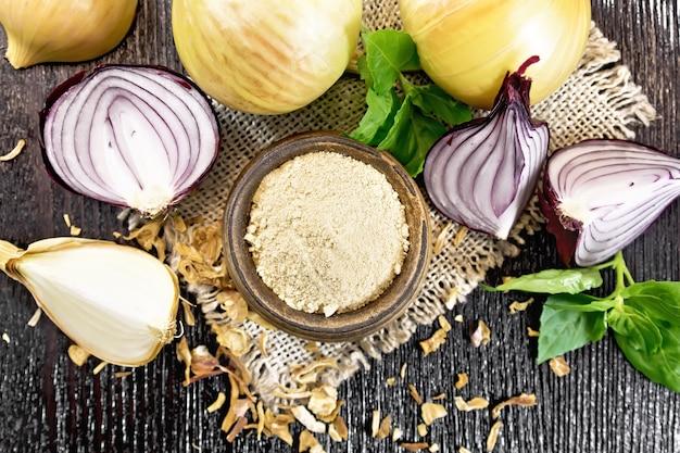 Poudre d'oignon dans un bol sur toile de jute, oignons violets et jaunes, flocons d'oignons séchés et basilic sur fond de planche de bois d'en haut