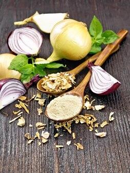 Poudre d'oignon et flocons séchés dans deux cuillères, oignons violets et jaunes, basilic sur fond de planche de bois
