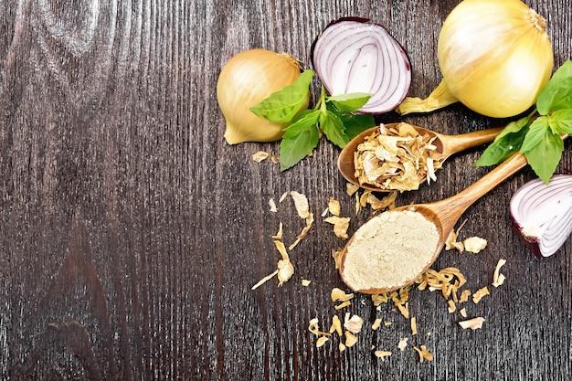 Poudre d'oignon et flocons séchés dans deux cuillères, oignons violets et jaunes, basilic frais sur fond de planche de bois foncé d'en haut