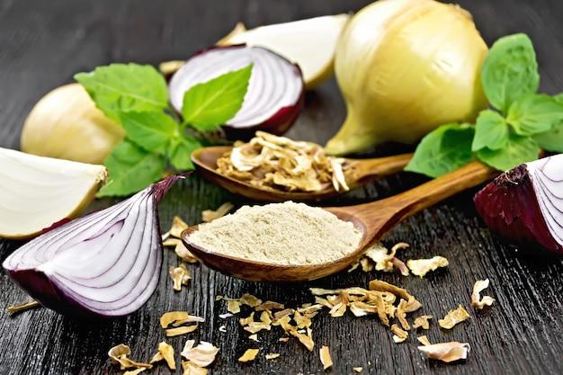 Poudre d'oignon et flocons séchés dans deux cuillères, oignons violets et jaunes, basilic frais sur fond de planche de bois foncé