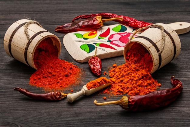 Poudre de paprika rouge doux et chaud magyar. motif traditionnel sur une planche à découper, différentes variétés de poivre sec. bois noir