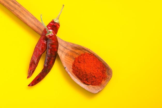 Poudre de piment dans une cuillère en bois avec froid rouge sec sur une surface jaune