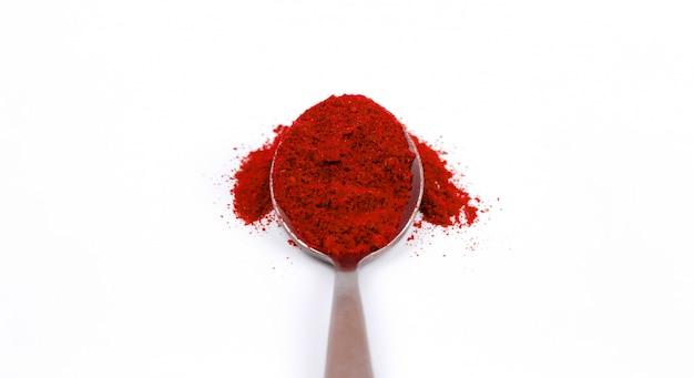 Poudre de piment rouge dans une cuillère en métal sur blanc